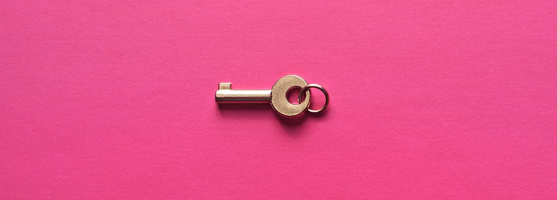 Avain messinkiä vaaleanpunaista taustaa vasten